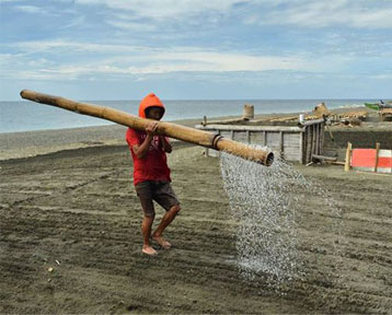 Fig. 4.  The Asindero watering the sand with seawater using large bamboo poles.  Photo by Norman Posecion which won the Grand Final in the 2nd PAGCOR National Photo Competition